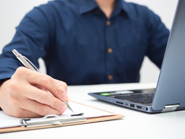 Mano ravvicinata dell'uomo che scrive sulla scheda del documento sul tavolo con il laptopwork from home concept