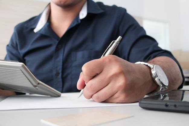 Chiuda sulla mano dell'uomo che scrive penna su carta e calcolatrice sinistra della holding in ufficio. concetto di ufficio di lavoro. concetto di lavoro. salaryman. conto o concetto finanziario.