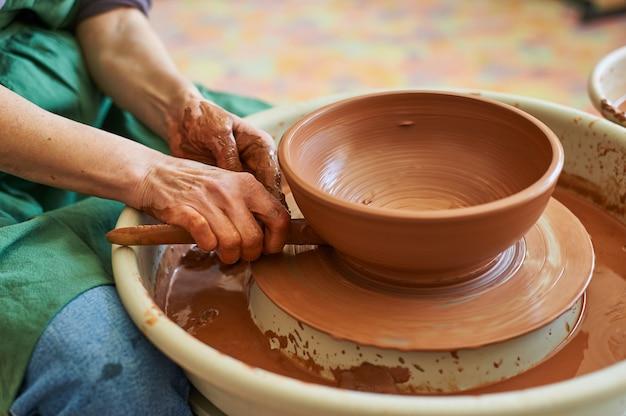 Primo piano della mano di un maestro vasaio che lavora su un cerchio con argilla