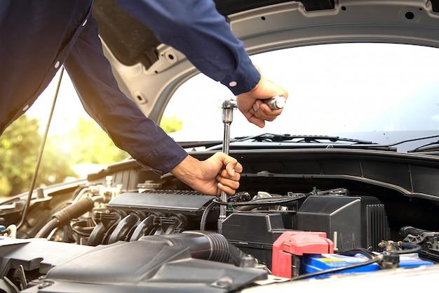 Chiuda sulla mano delle mani del meccanico facendo uso della chiave per riparare un motore di automobile. concetti di supporto e servizi di assicurazione auto.