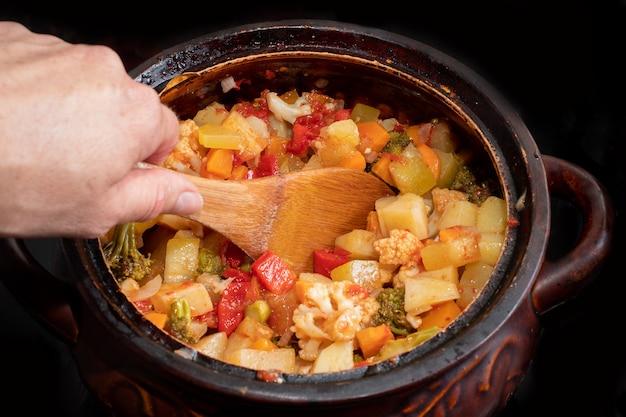 Close-up la mano mescola uno stufato di verdure in una pentola con un cucchiaio di legno. varie verdure tritate finemente stufate in una casseruola. concetto di cibo sano. concetto di cibo vegetariano