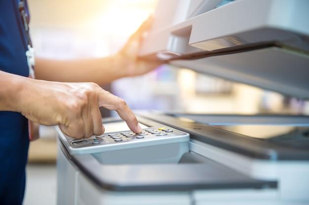 Chiudere la mano dell'uomo di ufficio premere il pulsante sulla fotocopiatrice.