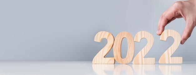 Close up pick mano felice anno nuovo 2022 giù sul tavolo bianco e sfondo grigio.festa celebrazione