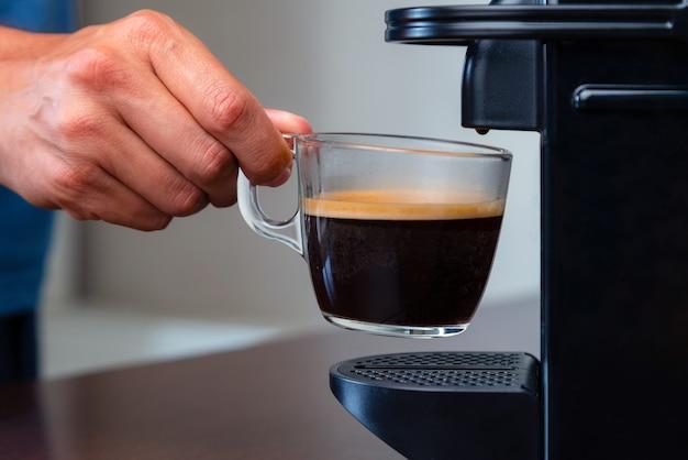 Stretta di mano raccogliendo una tazza di caffè espresso della macchina per il caffè in capsule a casa.