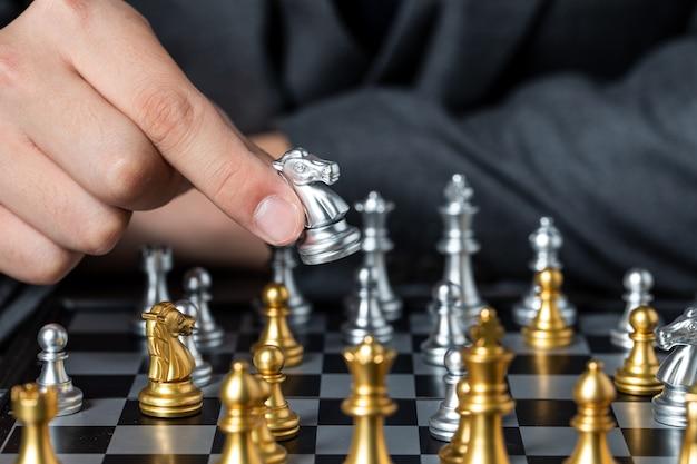 Primo piano a portata di mano giocando con pezzi degli scacchi in oro e argento