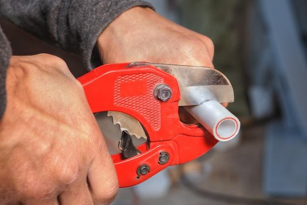 Primo piano dell'idraulico della mano usando la taglierina per tubi di plastica.