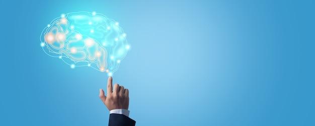 Primo piano del punto della mano sull'icona della connessione cerebrale attiva e idea di lavorare e pianificare su sfondo blu