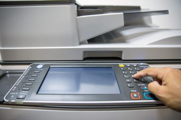 Close-up mano premere il pulsante sul pannello della fotocopiatrice