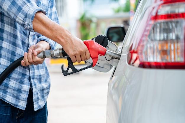 Mano ravvicinata di rifornire l'auto da soli, pompaggio del gas dell'attrezzatura alla stazione di servizio.