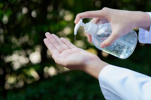 Chiuda sulla prevenzione dell'igiene delle mani pulite del gel dell'alcool del disinfettante della mano sfrega il virus del coronavirus