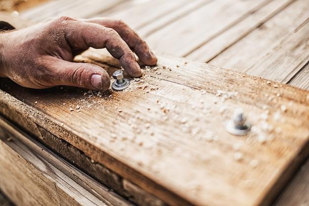 Stretta di mano avvitando un bullone in una tavola di legno