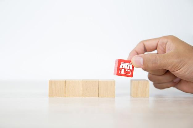 La mano del primo piano seleziona la pila di blocchi di legno con l'icona del negozio di affari in franchising.