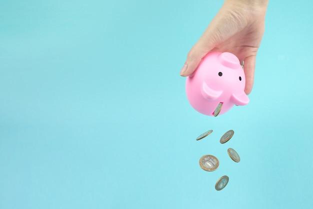 La mano ravvicinata scuote le monete dal salvadanaio rosa, monete che cadono. vendita, acquisto, risparmio dei consumatori, concetto di budget.