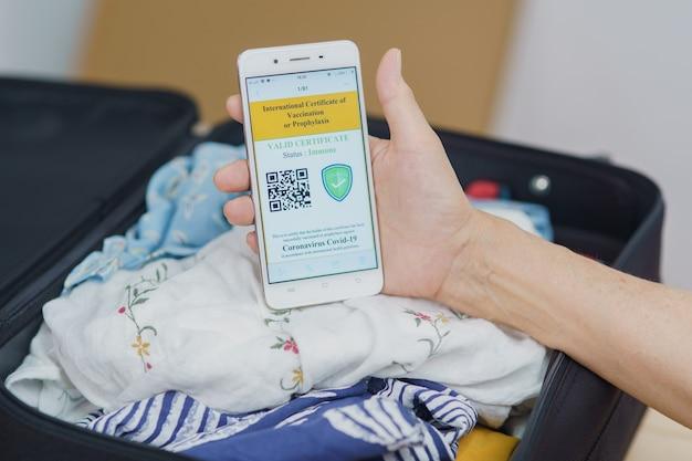 Mano ravvicinata che mostra lo schermo del telefono cellulare del passaporto del vaccino dell'immunità covid1