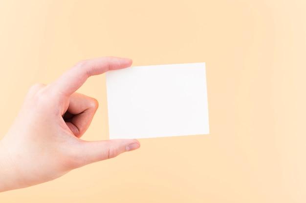 Mano del primo piano che mostra biglietto da visita di carta