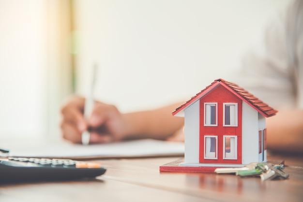 Primo piano del documento di prestito della firma della firma della mano alla proprietà della casa. mutui e investimenti immobiliari, assicurazioni sulla casa, sicurezza