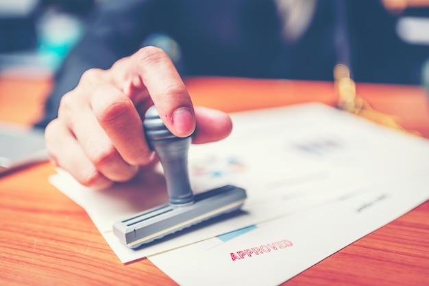 Timbratura della mano del primo piano dell'uomo d'affari per firma dell'approvazione sui documenti, concetto di affari