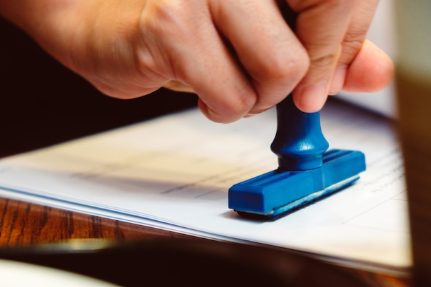 Mano del primo piano che timbra timbro di gomma sull'documenti, concetto di affari