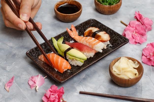 Stretta di mano tenendo il rotolo con le bacchette da un piatto in sushi bar