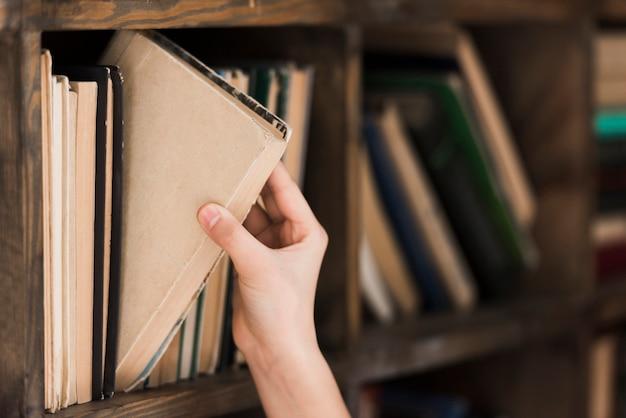 Mano del primo piano che prende il libro di storia dallo scaffale per libri