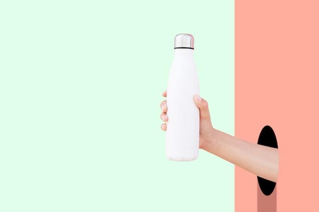 Primo piano della mano attraverso il foro che tiene la bottiglia di acqua termica d'acciaio riutilizzabile di eco di bianco contro le pareti rosse e verdi con lo spazio della copia.