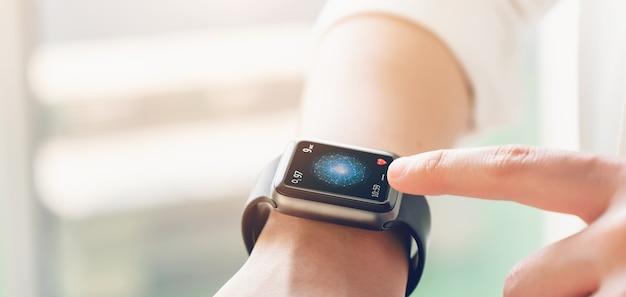 Primo piano dello smartwatch che tocca la mano con l'app per la salute sullo schermo, gadget per uno stile di vita attivo fitness