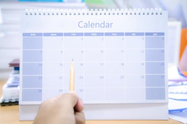Il primo piano usa la matita per puntare il calendario da tavolo vuoto.