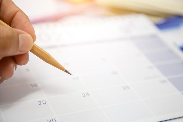 Matita di uso della mano del primo piano che prende nota sul calendario da scrivania in bianco.