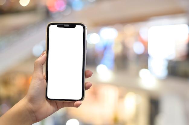 Chiudere la mano utilizzando lo smartphone in background centro commerciale