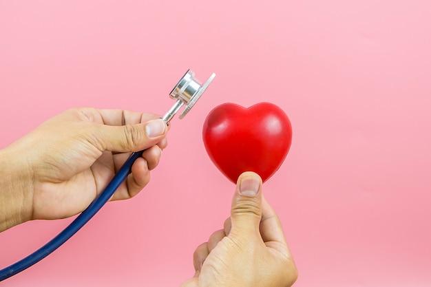 Chiuda sulla mano facendo uso dello stetoscopio che controlla un cuore. concetti un esame fisico e assicurazione sanitaria.