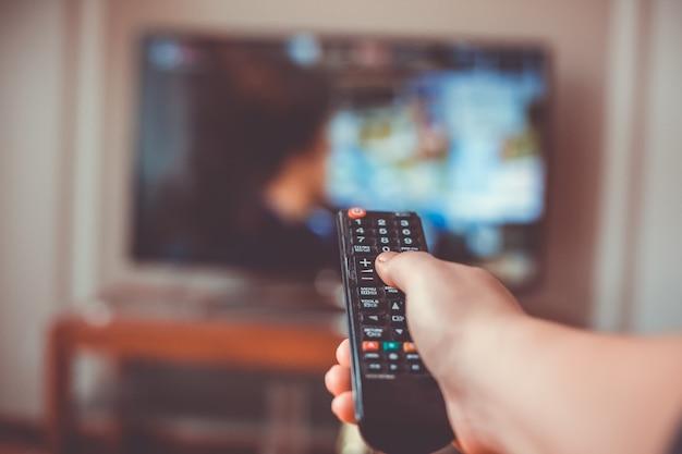 Primo piano della mano con il telecomando della televisione e preme il pulsante