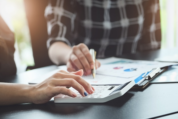 Chiuda sulla donna della mano che fa finanza e calcola sulla scrivania sui costi in ufficio.