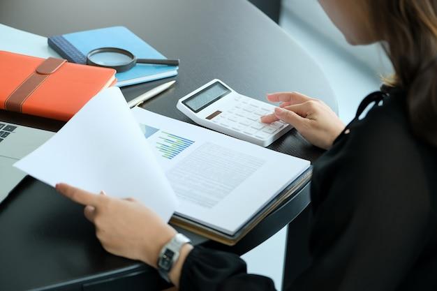 Chiuda sulla donna della mano che fa finanza e calcola sulla scrivania sui costi in ufficio