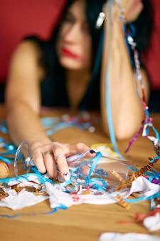 Primo piano di una donna che tiene in mano un bicchiere di champagne, dorme a tavola in una stanza disordinata dopo la festa di compleanno