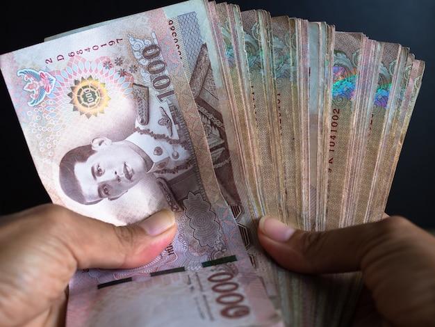 Chiuda sulla donna della mano che tiene una banconota tailandese di 1000 su priorità bassa nera per affari o finanza