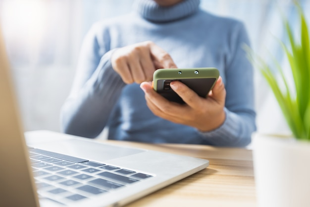 Mano ravvicinata di una donna che preme sul telefono, sulla tecnologia e sul nuovo concetto di vita normale