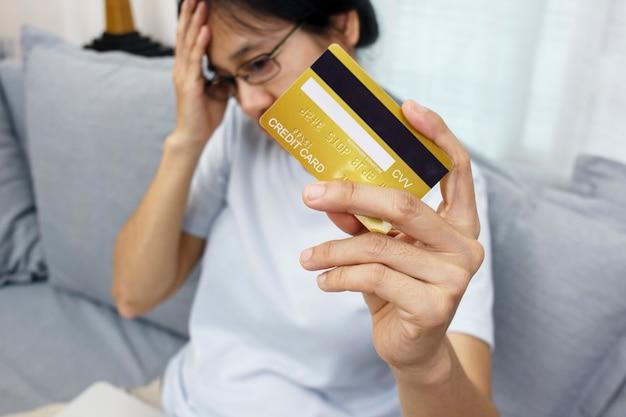 La mano ravvicinata delle donne tiene la carta di credito sentendosi stressata infelice e preoccupata per l'onere del pagamento del debito fiscale della ricevuta di un problema di acquisto eccessivo dallo shopping online. Foto Premium