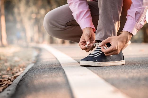 Vicino la mano di un giovane legare i lacci delle scarpe da ginnastica vicino al bordo della strada nel parco pubblico