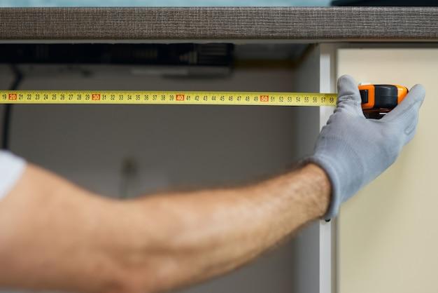Stretta di mano di un giovane idraulico professionista riparatore che utilizza un metro a nastro mentre si fa l'impianto idraulico