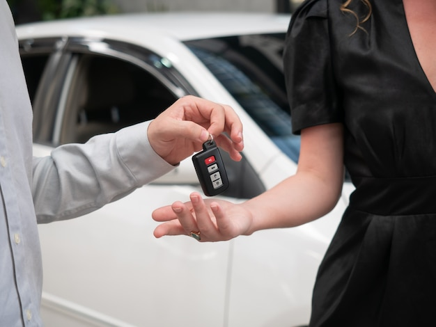 Primo piano di consegna delle chiavi per un'auto a un giovane imprenditore.