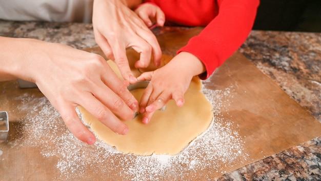 Primo piano delle mani di un adulto e di un bambino che ritagliano i biscotti dall'impasto