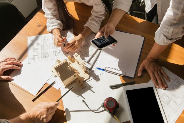 Chiudere le mani di architetto-ingegnere e giovane coppia durante la presentazione della futura casa. tabella vista dall'alto con documenti, progetto. prima casa, industriale, concetto di costruzione. trasferirsi in un nuovo luogo dal vivo.
