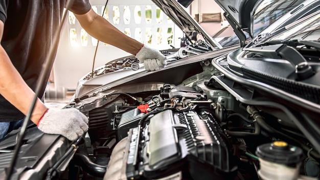 Mani del primo piano del meccanico automatico utilizzando la chiave per la manutenzione del motore dell'auto.