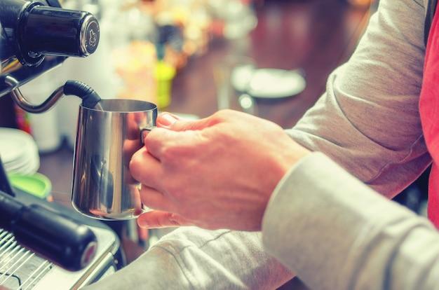 Primo piano delle mani barista fruste latte per caffè espresso alla macchina del caffè in un accogliente bar. focalizzazione morbida.