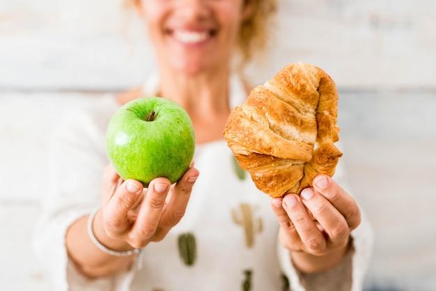 Primo piano delle mani di una bella donna sullo sfondo che tiene cibo come croissant e mela - scegliendo il suo stile di vita e il suo pasto - dieta e uno stile di vita sano
