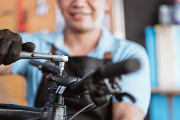 Primo piano delle mani di un meccanico di biciclette che indossa i guanti utilizzando una chiave antiurto per rimuovere i bulloni