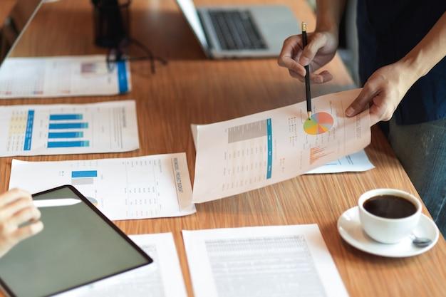 Consulenza ravvicinata delle mani nella sala riunioni con laptop per report finanziari tablet