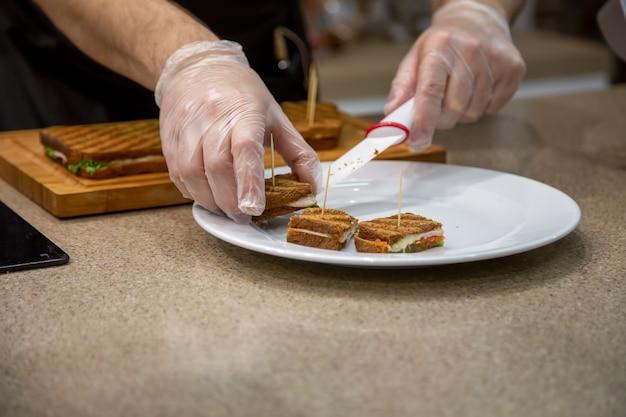 Primo piano delle mani di un cuoco in guanti di gomma messo su un piatto bianco snack panini alla griglia. primo piano, messa a fuoco morbida, lo sfondo è la cucina sfocata