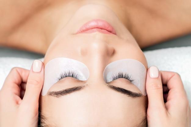 Chiudere le mani del cosmetologo colla nastro sotto gli occhi della giovane donna prima della procedura di estensione delle ciglia.