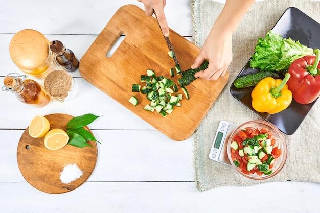 Chiudere le mani che tagliano il cetriolo, preparando per un pasto sano con peperoni e pomodori.